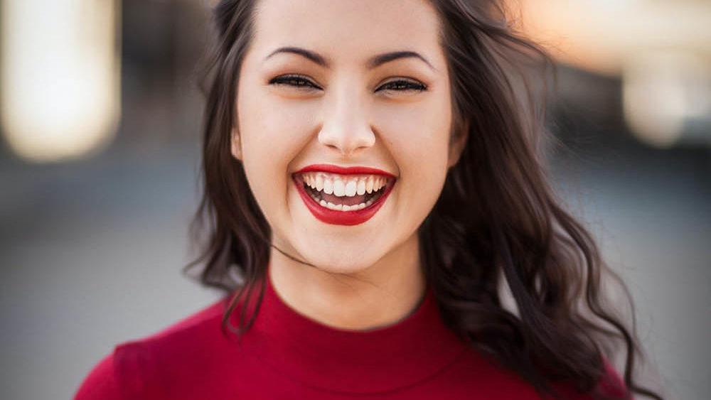 en smilene kvinne med en rød genser, rød er en sterk primærfarge som er tilbake i mote