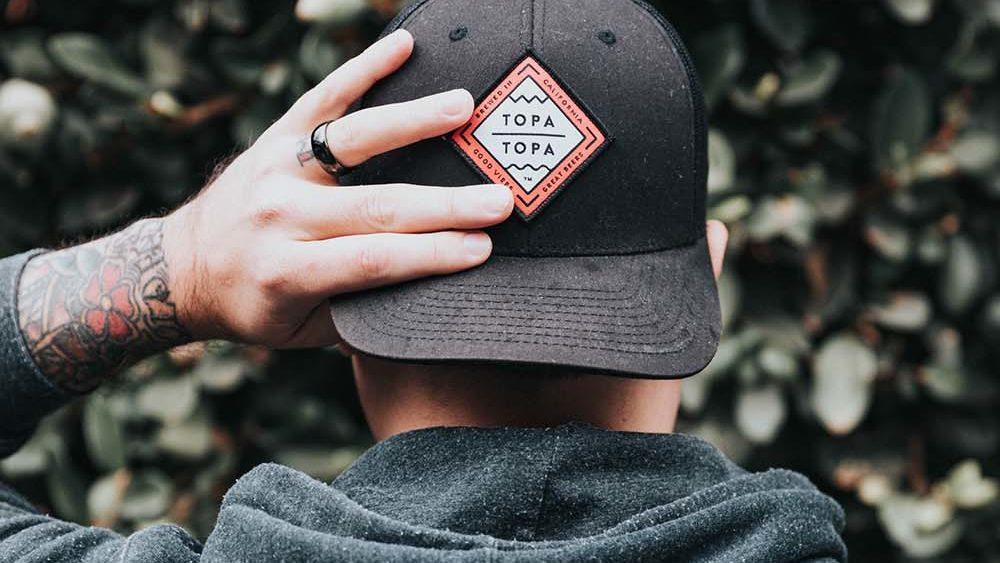 en mann som holder på sin svarte logo caps, til høsten 2021 er det fritt frem med dine favoritt capser