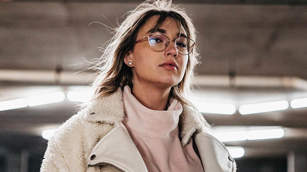 kvinne med en lystonet fuzzy jakke, til høsten 2021 er det koselige og fluffy jakker som er trenden